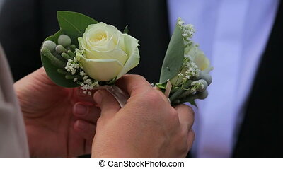 Woman Pinning Boutonniere On Guest Jacket