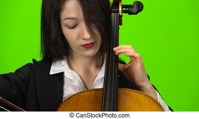 Woman pins the cello with her fingers. Green screen. Close...