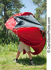 woman pitching tent - young woman trying to pitch red tent