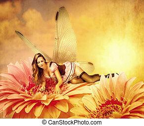 woman pixie lies on a summer flower