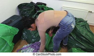 Woman places clothes in a green plastic bag