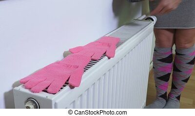 Woman places wet gloves and hat on radiator