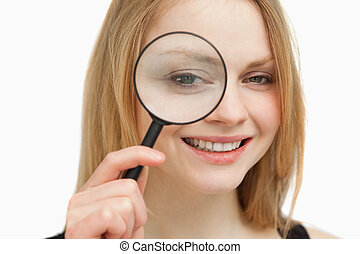 Woman placing a magnifying glass on her eye