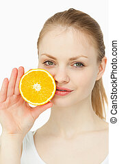 Woman placing an orange on her lips against white backgroun