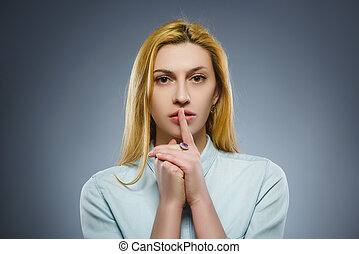 woman placing finger on lips asking shh, quiet, silence on gray background