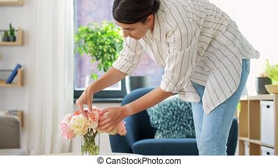woman placing flowers on coffee table at home - household, ...