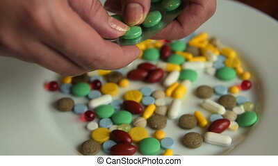 Woman placing pills on dinner plate. Medicine abuse, overdose