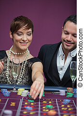 Woman placing roulette bet with man