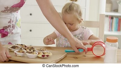 Woman placing tray of muffins in front of child - Arm of...