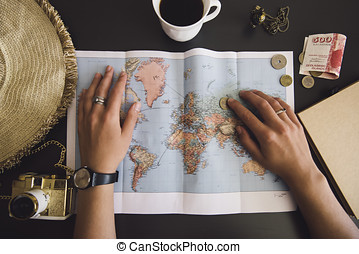 Woman planning her trip. Human hands on the world map with the hat, film camera, some money, notebook from recycled paper and freshly brewed coffee cup on the dark wooden table background.
