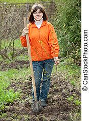woman plants tree in garden - Young woman plants tree in ...