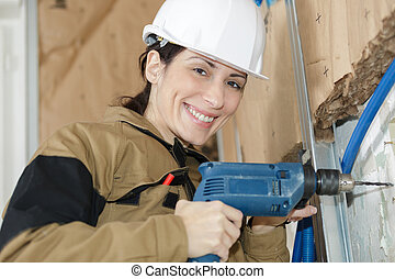 woman plasterer drilling the wall