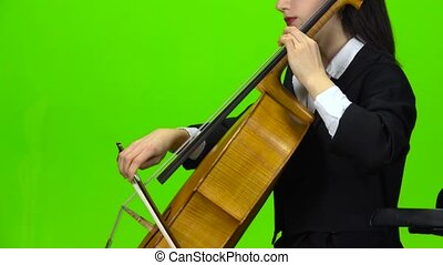 Woman play cello. Green screen. Side view. Close up - Woman...