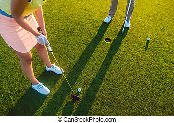 Woman player ready to hit the ball into the hole at the end of a game
