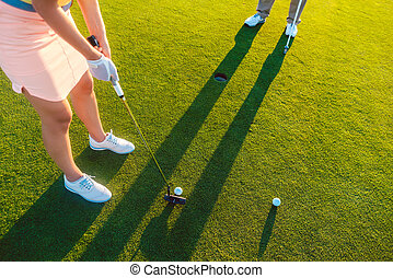 woman player ready to hit the ball into the hole at the end of a