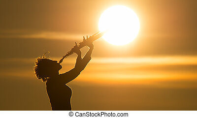 Woman playing a saxophone at the sun
