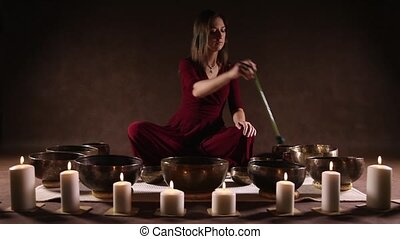 Woman playing a singing bowls in front of brown background...