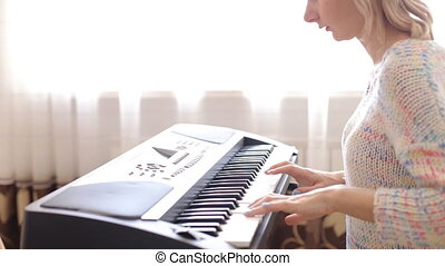 Woman playing a synthesizer - close-up video of a woman hands