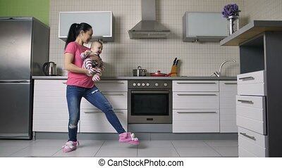 Woman playing and dancing with baby son in kitchen
