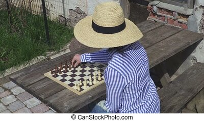 Woman playing chess outdoors