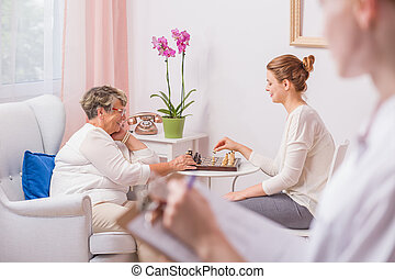 Woman playing chess with mother