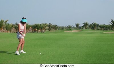 People, sports, leisure activities, recreation and lifestyle, golf in country club during summer holiday. Asian woman hitting ball with iron in golf course. 11of30
