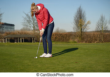 Woman playing golf lining up a putt