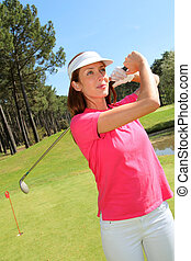 Woman playing golf on a sunny day