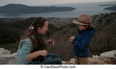 Woman playing guitar and little boy on cliff in overcast day.