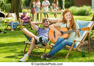 Woman playing guitar in garden