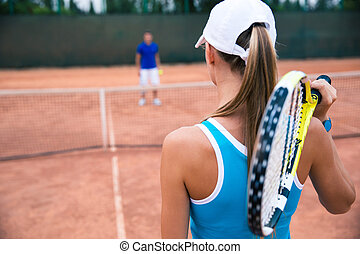 Woman playing in tennis with man outdoors