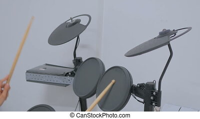 Woman playing on electronic drum set