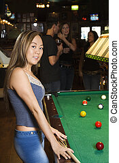 Woman playing pool.