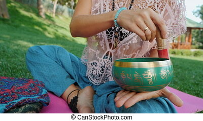 Woman playing singing bowl while sitting on pink yoga mat in park at summer. Vintage tonned. Beautiful girl with mala beads meditating on green grass. Slow motion.