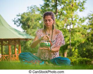 Woman playing singing bowl while sitting on pink yoga mat in...