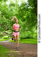 Woman playing sports, running in the park