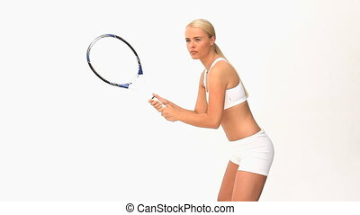 Woman playing tennis against a white background