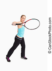 Woman playing tennis with a racket against white background