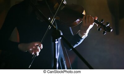Woman playing the violin at rock concert, telephoto