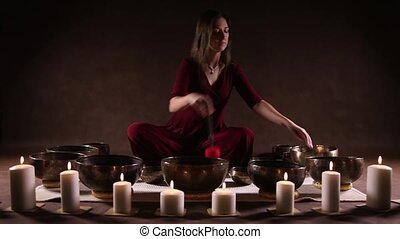 Woman playing Tibetan bowls - Young woman relaxing with...
