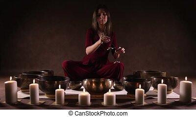 Woman playing tingsha (Tibetan bell - Woman playing Tibetan...