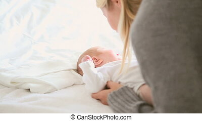 Woman playing with a baby who is lying on a bed