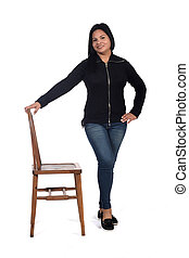 woman playing with a chair in white background, front view,