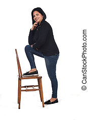 woman playing with a chair in white background, hand on chin and foot on the chair