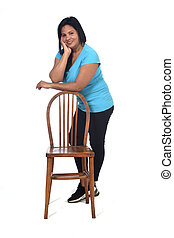 woman playing with a chair in white background, leaning on the chair