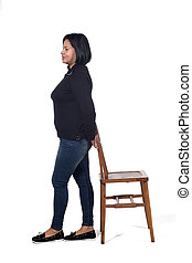 woman playing with a chair in white background, profile