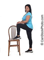 woman playing with a chair in white background, with the foot in the chair and looking at camera