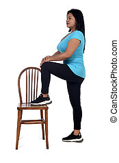 woman playing with a chair in white background, with the foot in the chair