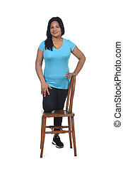 woman playing with a chair in white background, with the knee in the chair