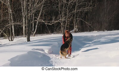 Woman playing with a dog on a snow
